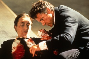 Mr. White (Harvey Keitel) inspects the wounds of Mr. Orange (Tim Roth) in Reservoir Dogs.